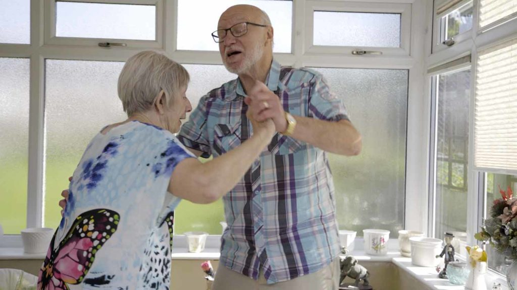 a photo of an older couple dancing in their kitchen. They are wearing normal clothes