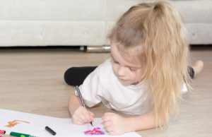 a small girl with blond hair lays on her stomach, hold a pencil and is drawing