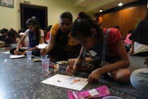 women and girls sit on the floor and draw on a piece of paper