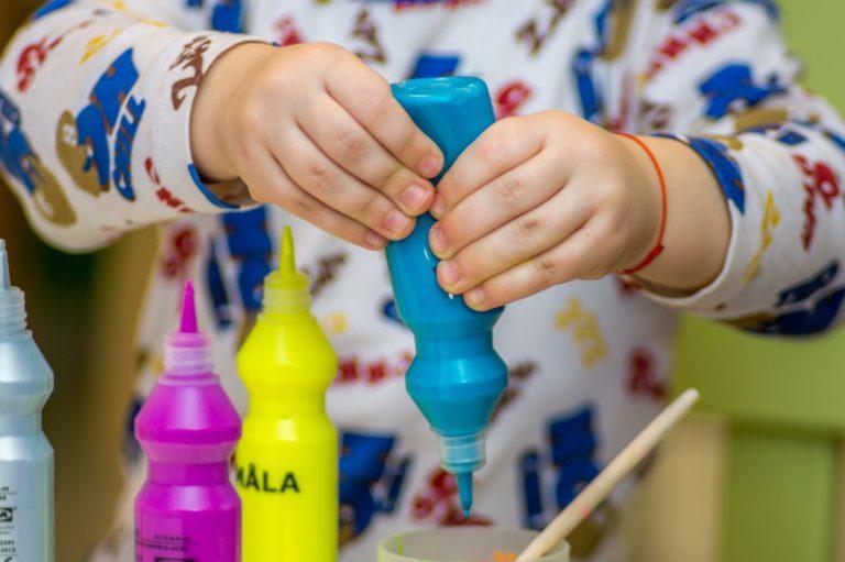 kid squeezing blue paint bottle
