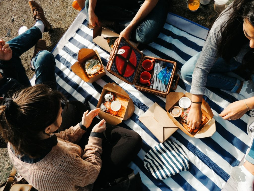 4 people sat around a picnic bbasket on a stripy blanket with breakfast