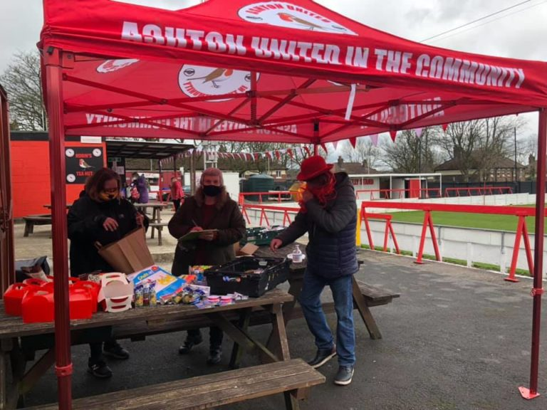Food bank set up by Ashton United during lockdown. 3 people are under an Ashton United tent, with food parcels for vulnerable people.