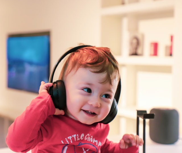 small, very happy kid listening to a podcast through big headphones