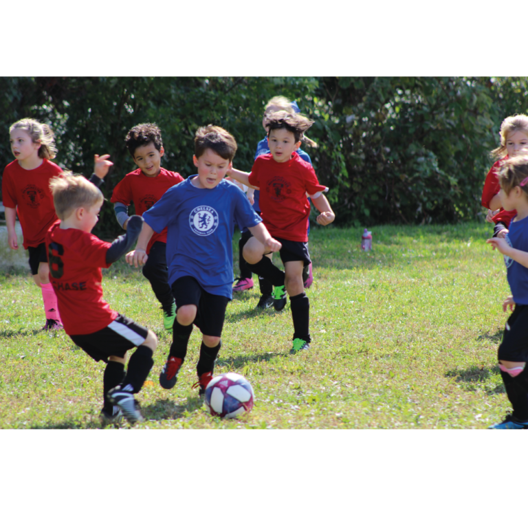 Kids playing football on a field in red and blue kits